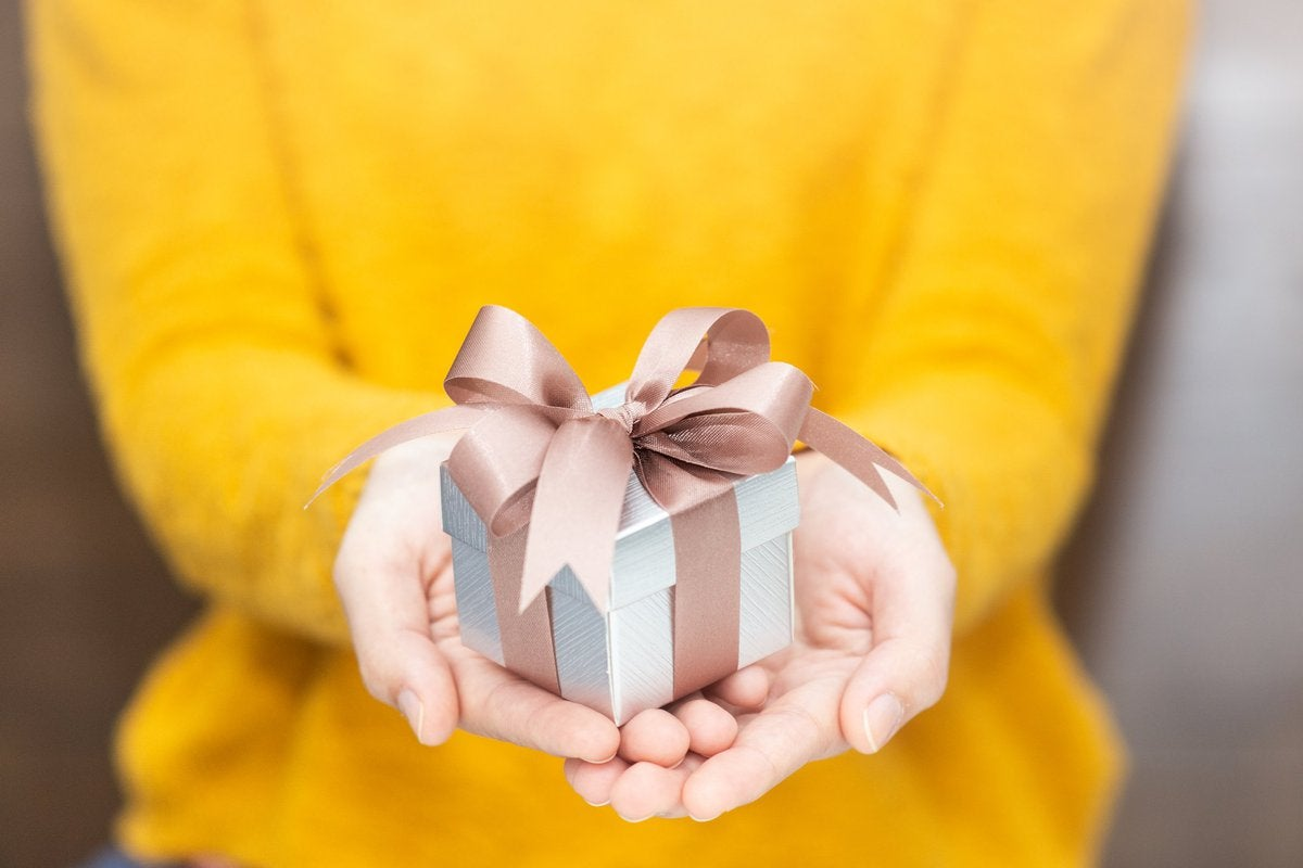 A woman in a yellow sweater holding out a wrapped gift.