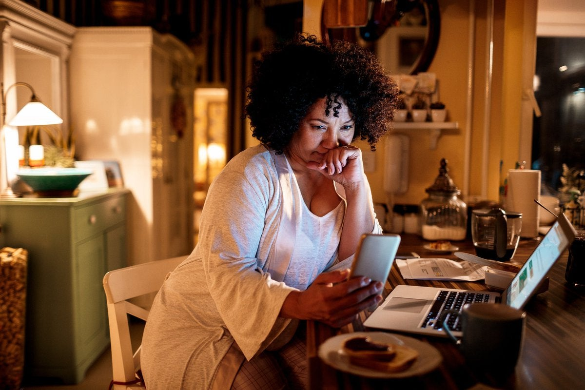 A woman in her kitchen sits at the island, using her phone and laptop.