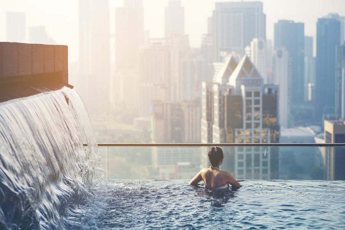 Woman standing in a rooftop pool overlooking a city.
