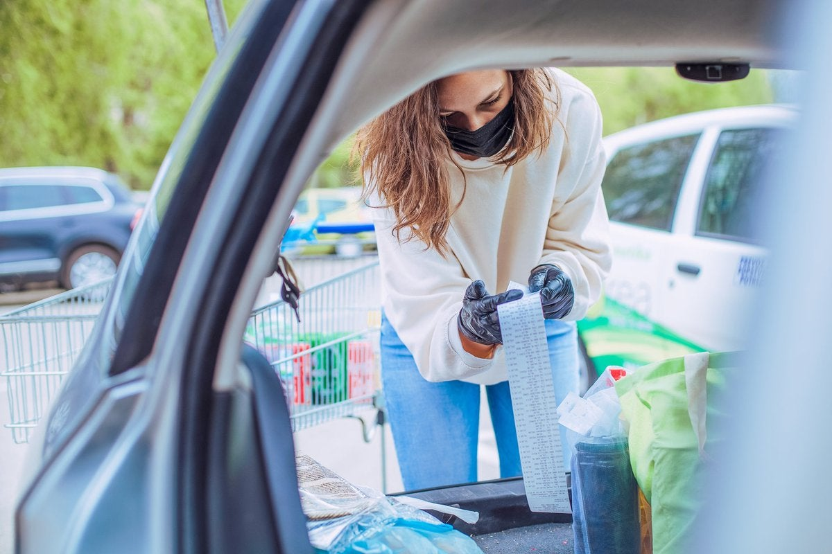 Woman loading car with groceries looks over her receipt closely.