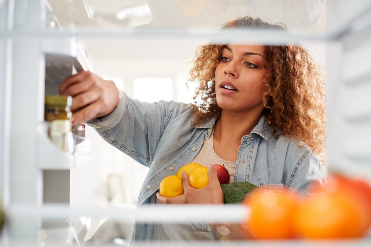 A woman putting fruits and vegetables away in her refrigerator.