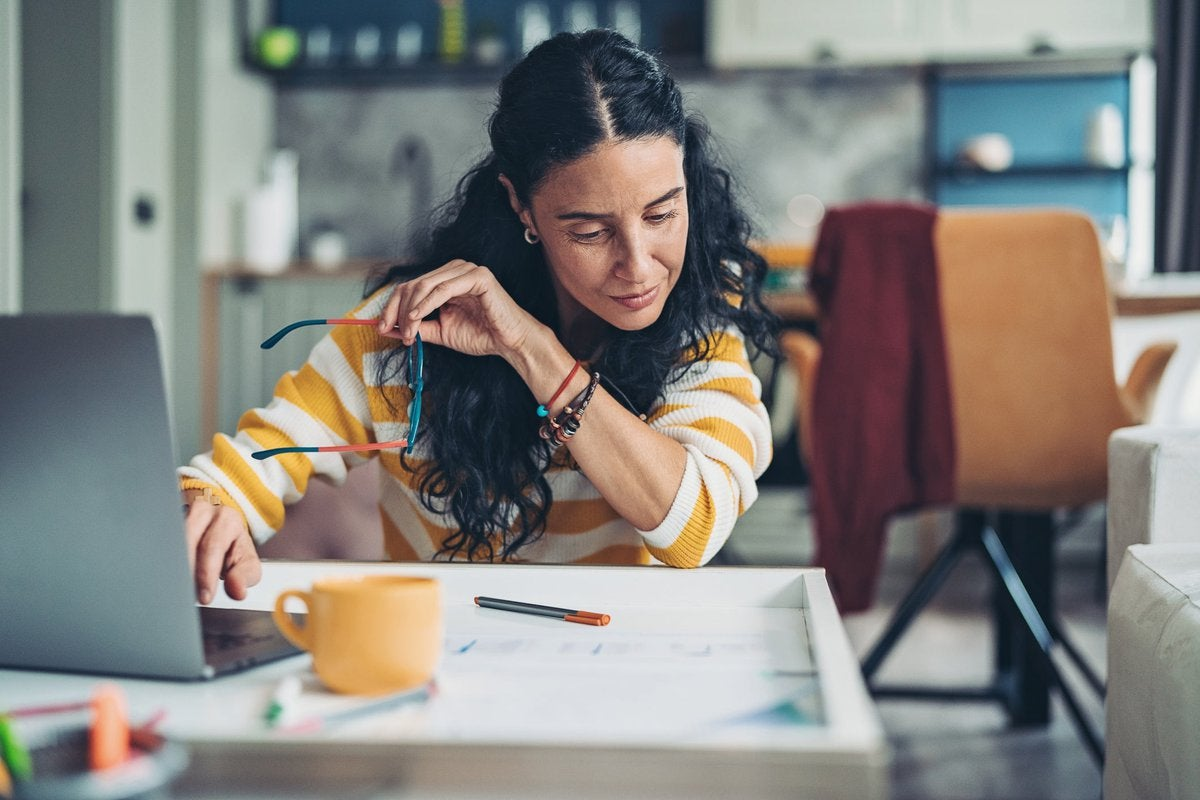 A woman sits at home, looking over her personal finances.