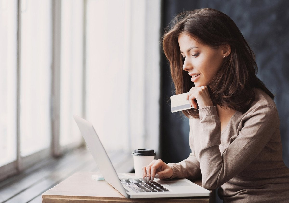 A woman sitting in front of a window while typing on a laptop with one hand and holding a credit card with the other.