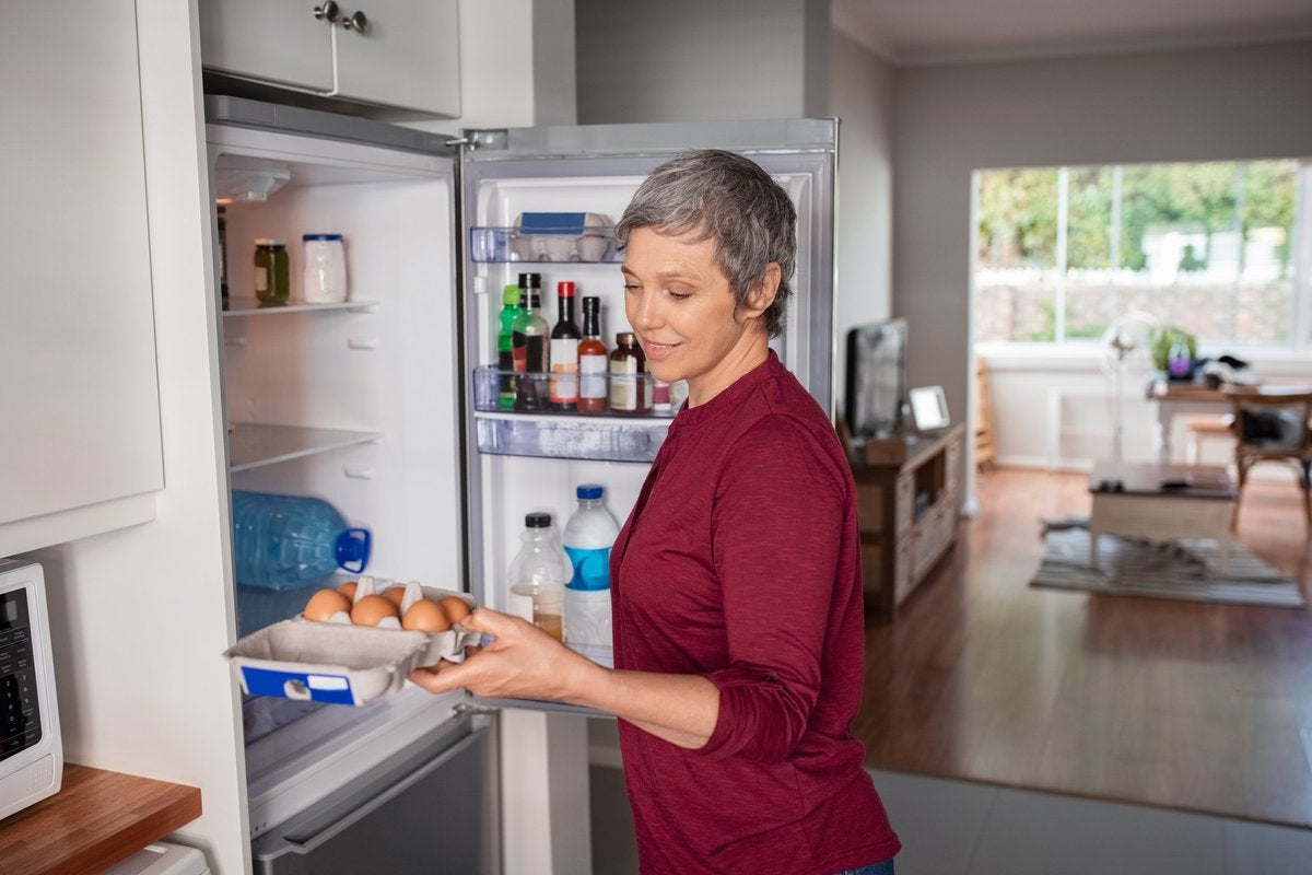 A woman opening the refrigerator and pulling out eggs.