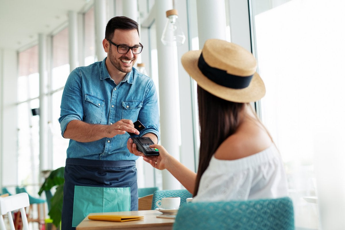 A young woman in a hat paying a waiter with her credit card.