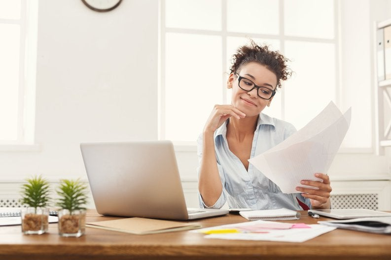 A woman reading documents at a desk.