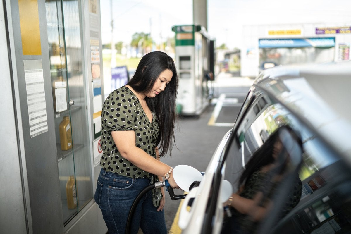 Woman refueling her car at a gas station.
