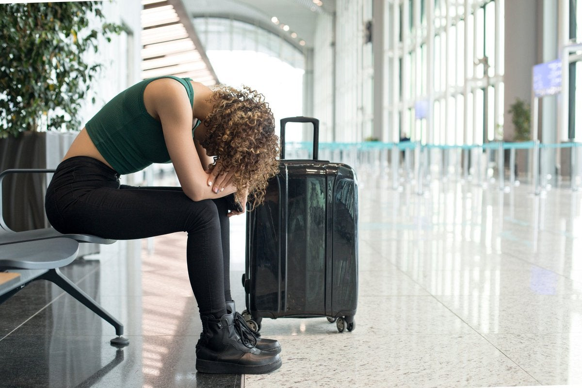 A woman sits dejectedly at the airport.