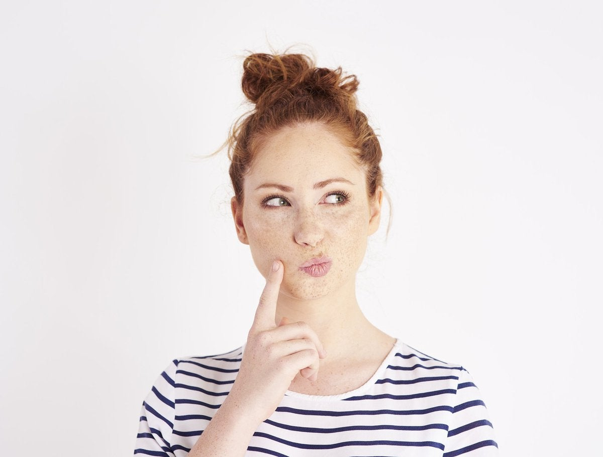 Woman thinking with her pointer finger resting on her cheek