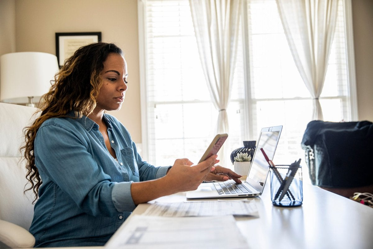 Woman using laptop and smartphone at home