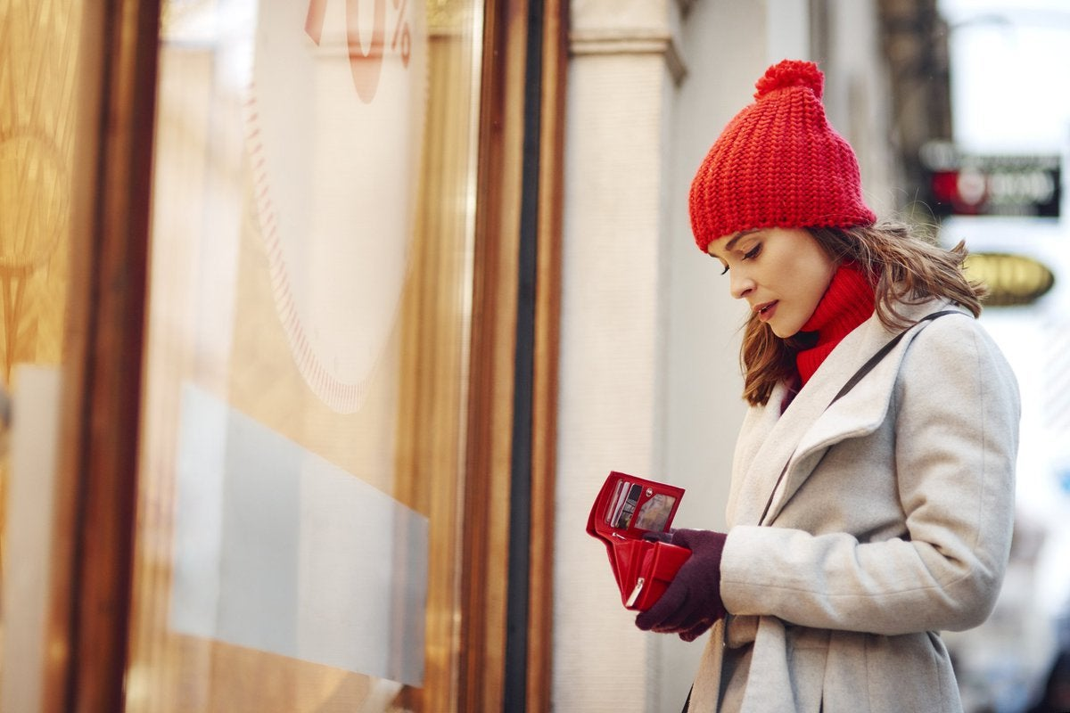 A woman in a winter hat looking at her empty wallet outside of a store.