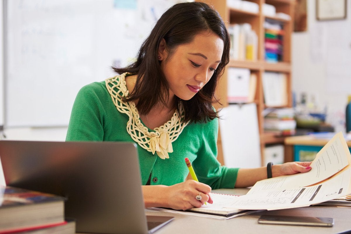 A woman reviewing paperwork at her desk.