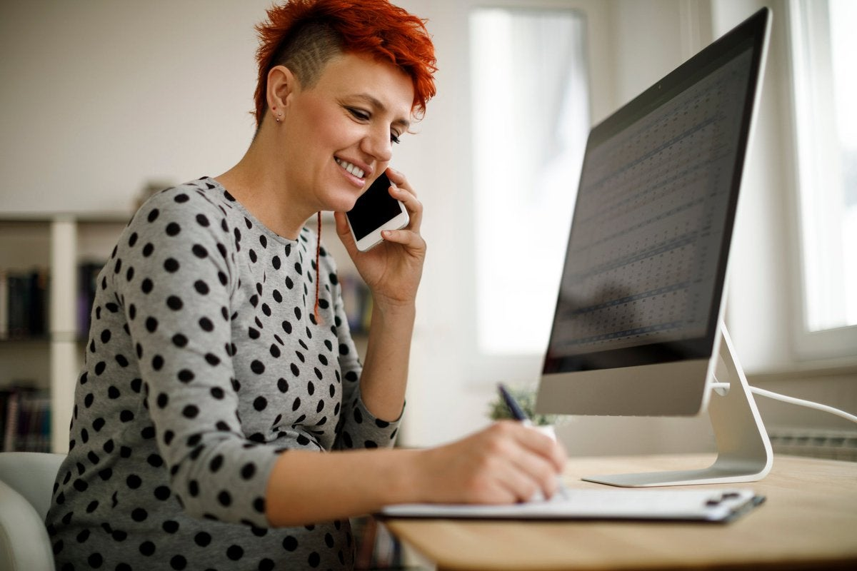 Woman working from home using computer, phone, and laptop.