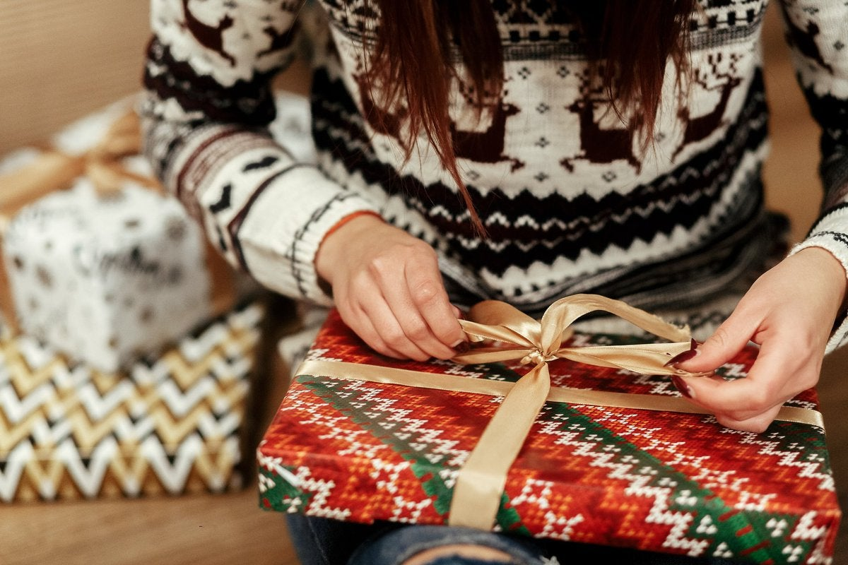A woman in a festive sweater wrapping gifts.