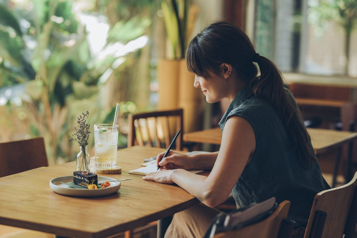 Woman writes letter at cafe table.