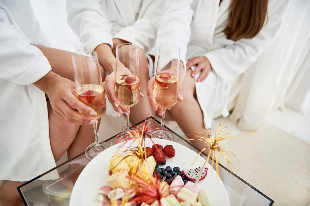 Three women in spa bathrobes with Champagne and a plate of fruit.