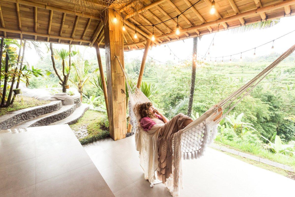 A women in a hammock on a tropical patio.