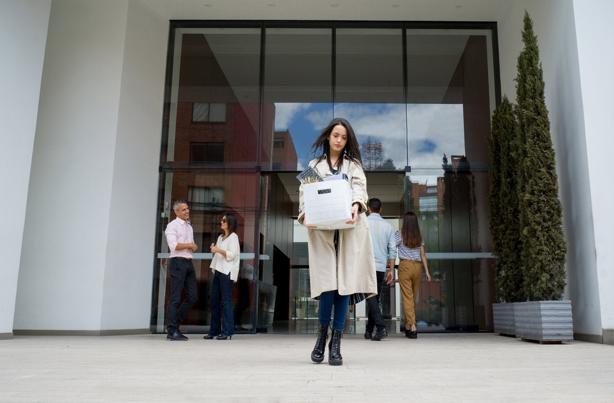 Woman leaving the office with her belongings in a box.