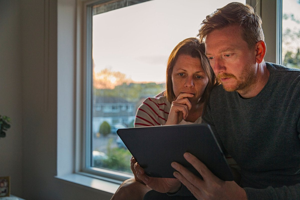 Worried-looking couple looking at a tablet together.