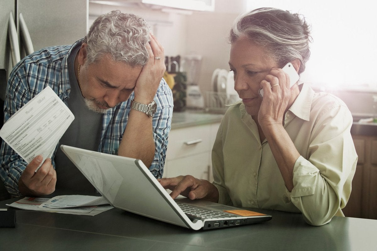 Worried looking mature couple with documents, phone, and laptop.