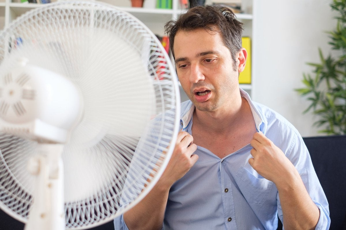 Man suffering from extreme heat sitting in front of fan.