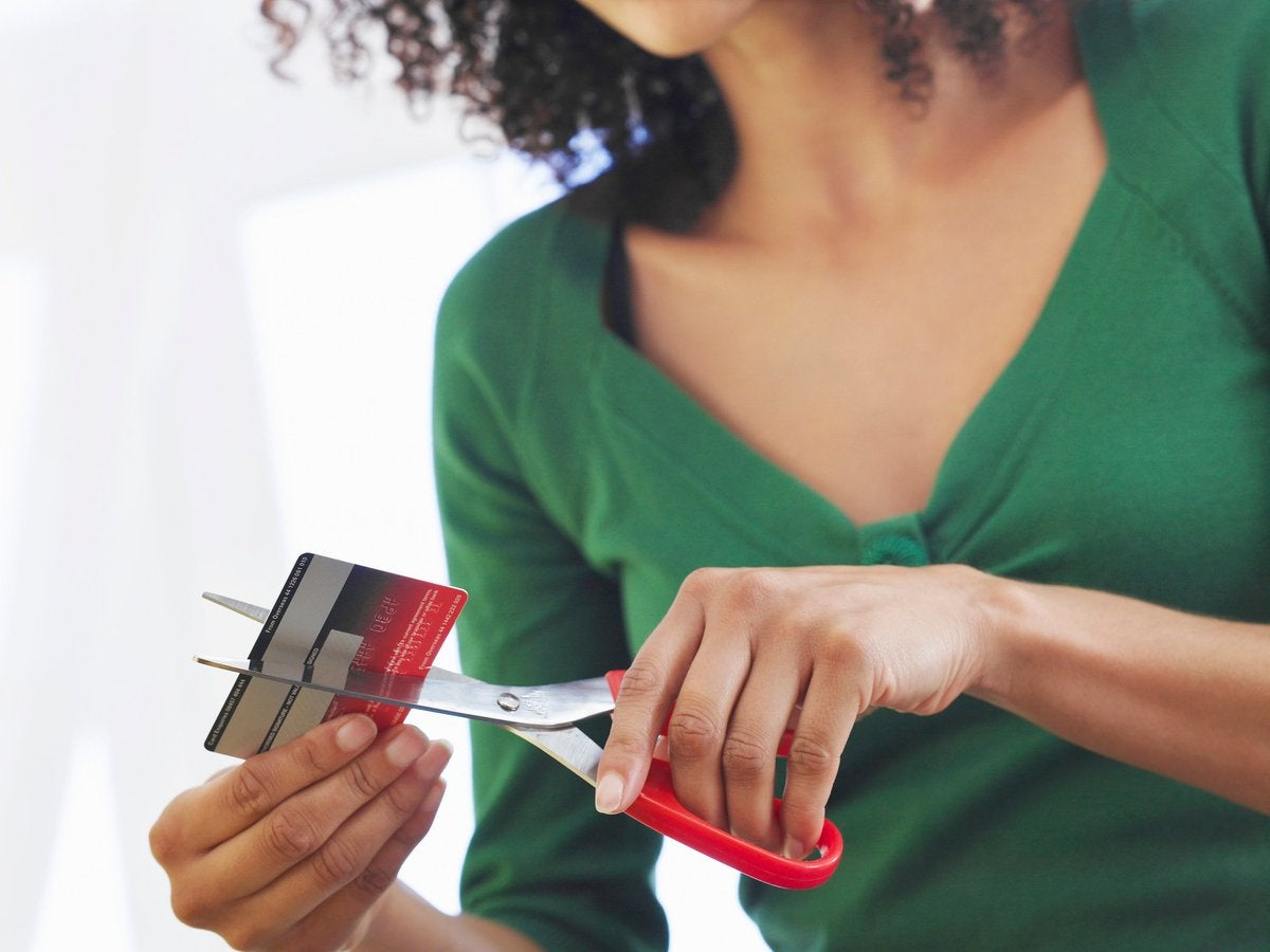 Young Woman Cutting Debit Card With Scissors