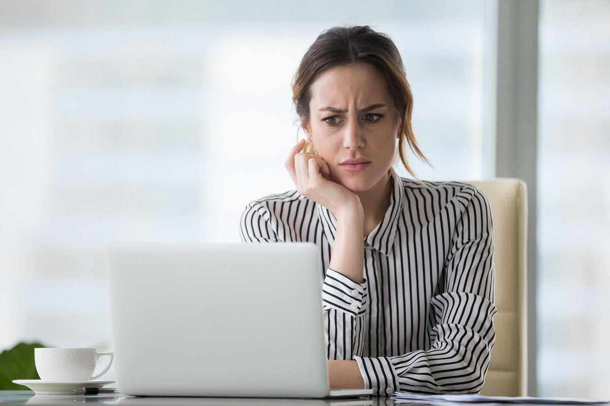 Young Woman Looking Surprised At Her Laptop