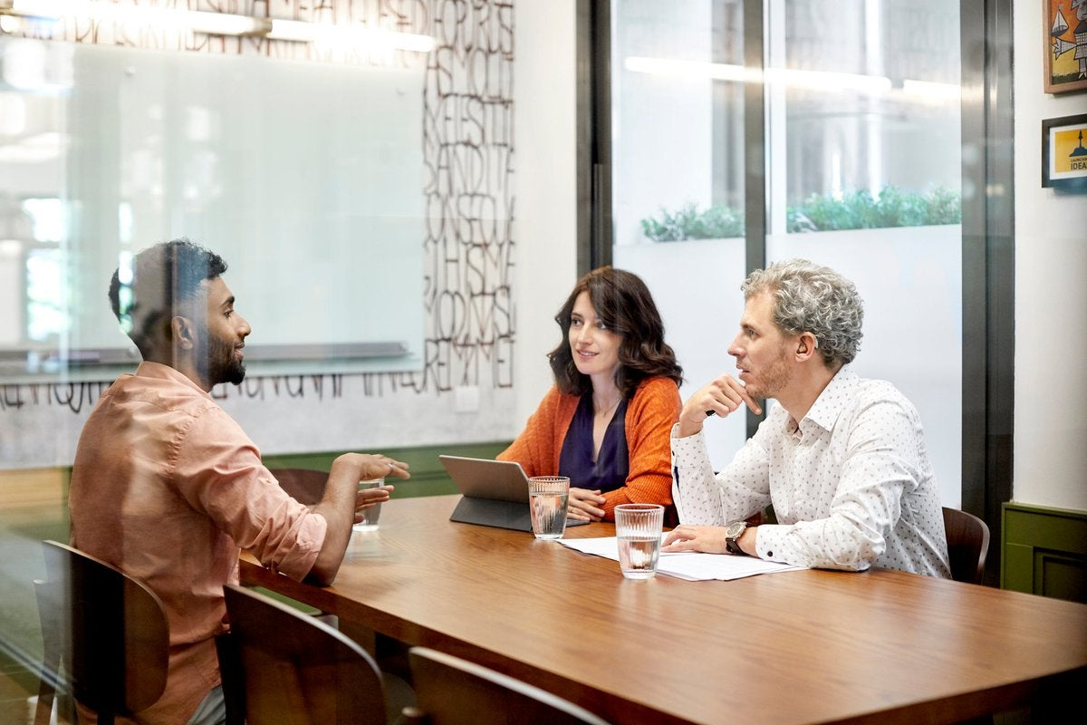 Young adult male is interviewed by two people in an office.