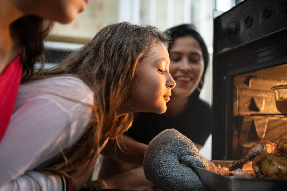 A young girl and her parents check on a turkey in the oven