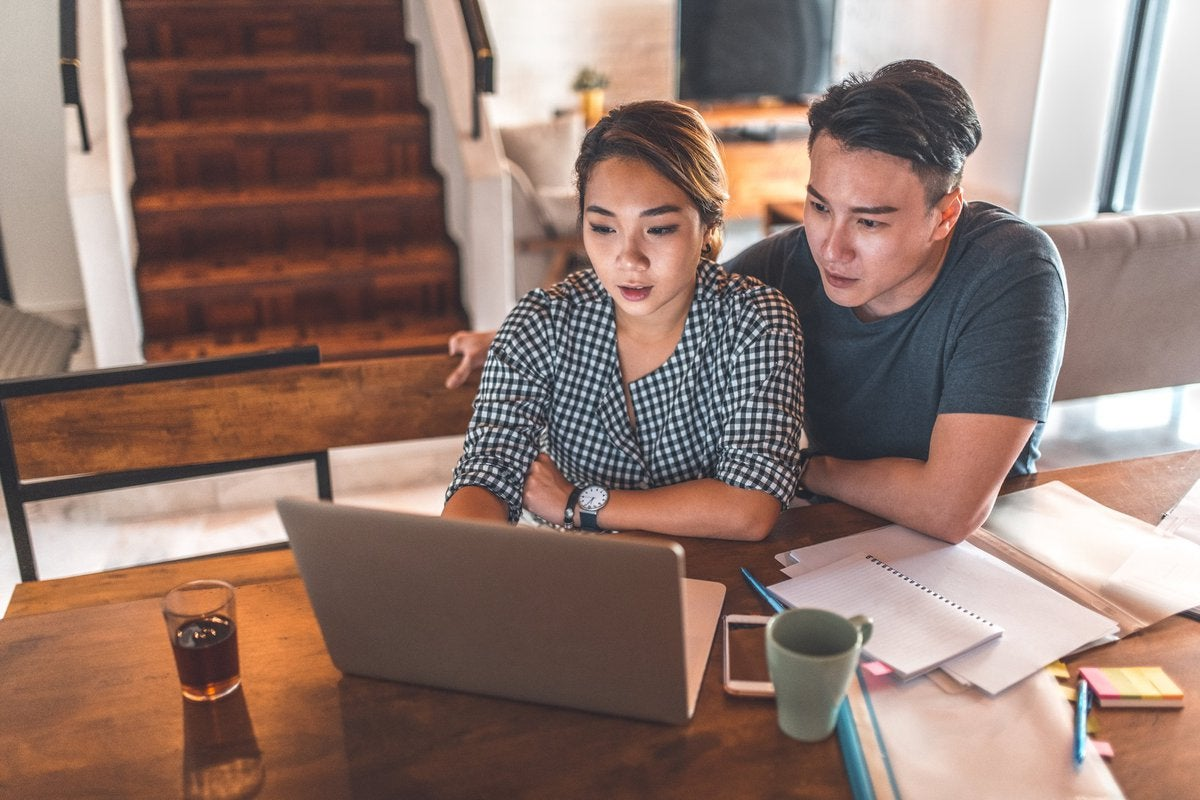 A young couple sitting at their dining table with notebooks and reviewing their finances on a laptop.