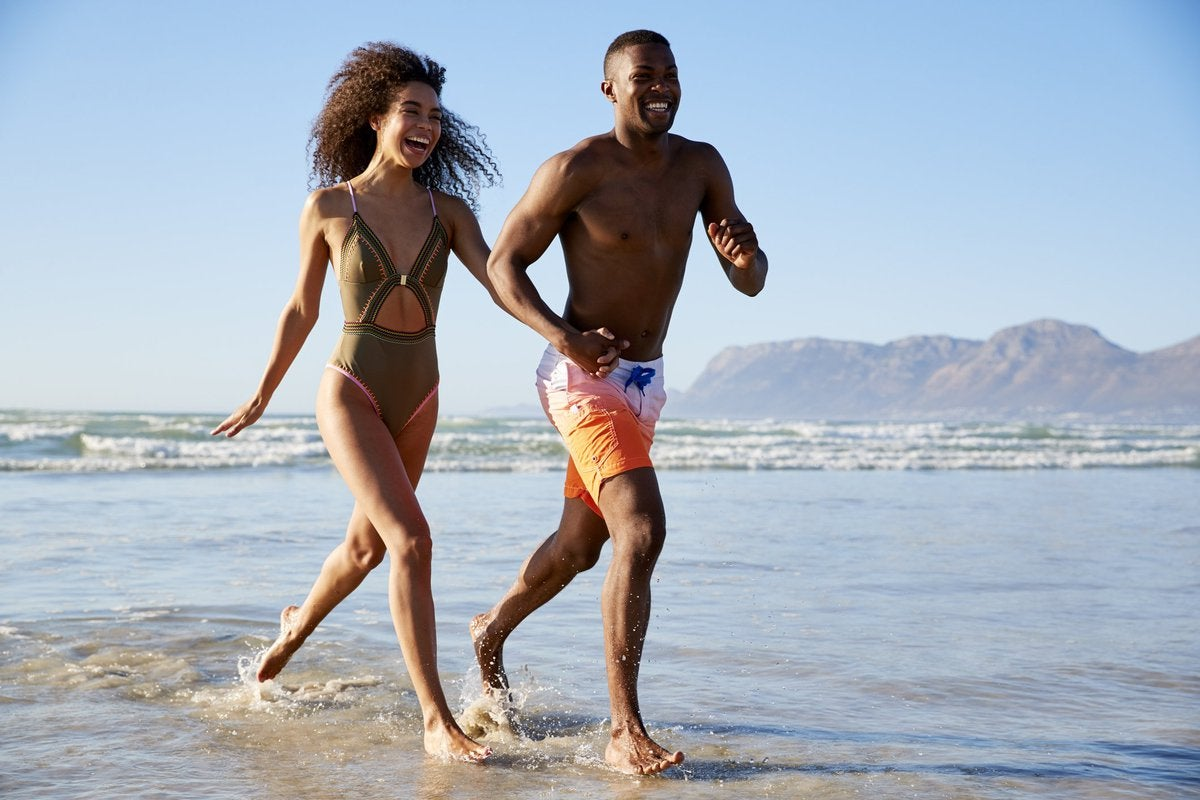 Young laughing couple in swimsuits running along the beach.