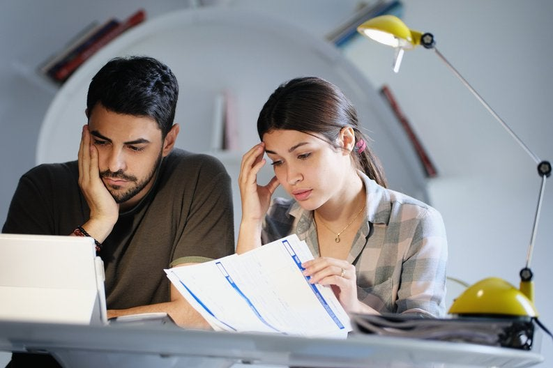 A young couple sitting at a desk and looking sadly at their bills.