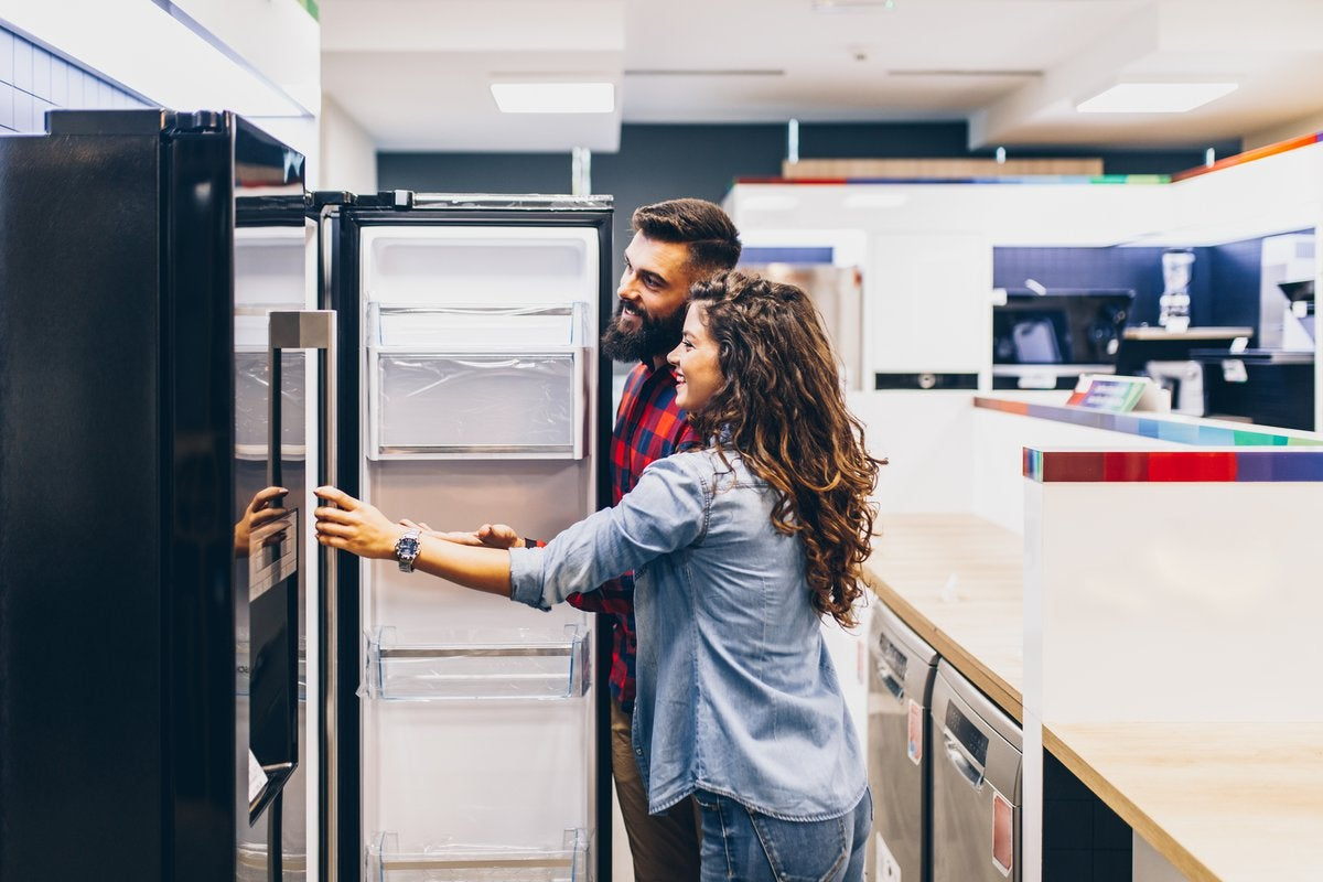 A young couple shopping for a new refrigerator at an appliance store.