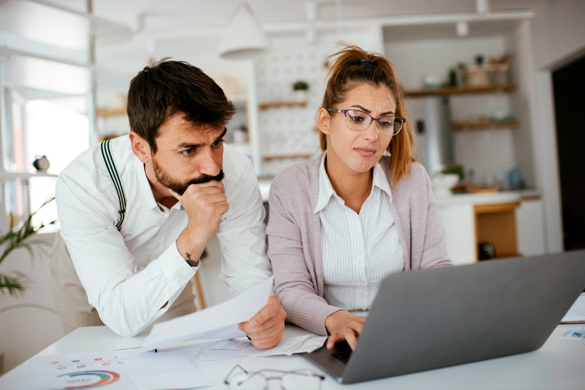 Young couple skeptically looks at information on a laptop screen