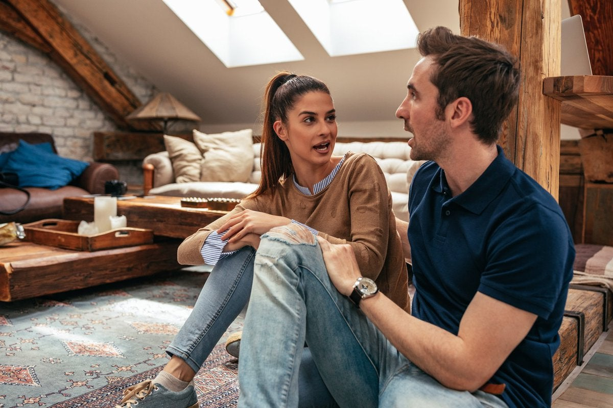 A young couple having a serious discussion sitting on their living room floor.