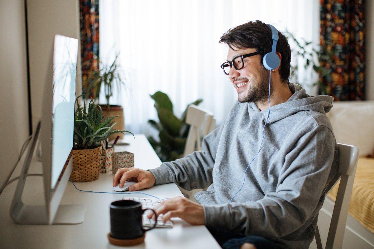A young daytrader sits at his desk at home, looking at his computer.