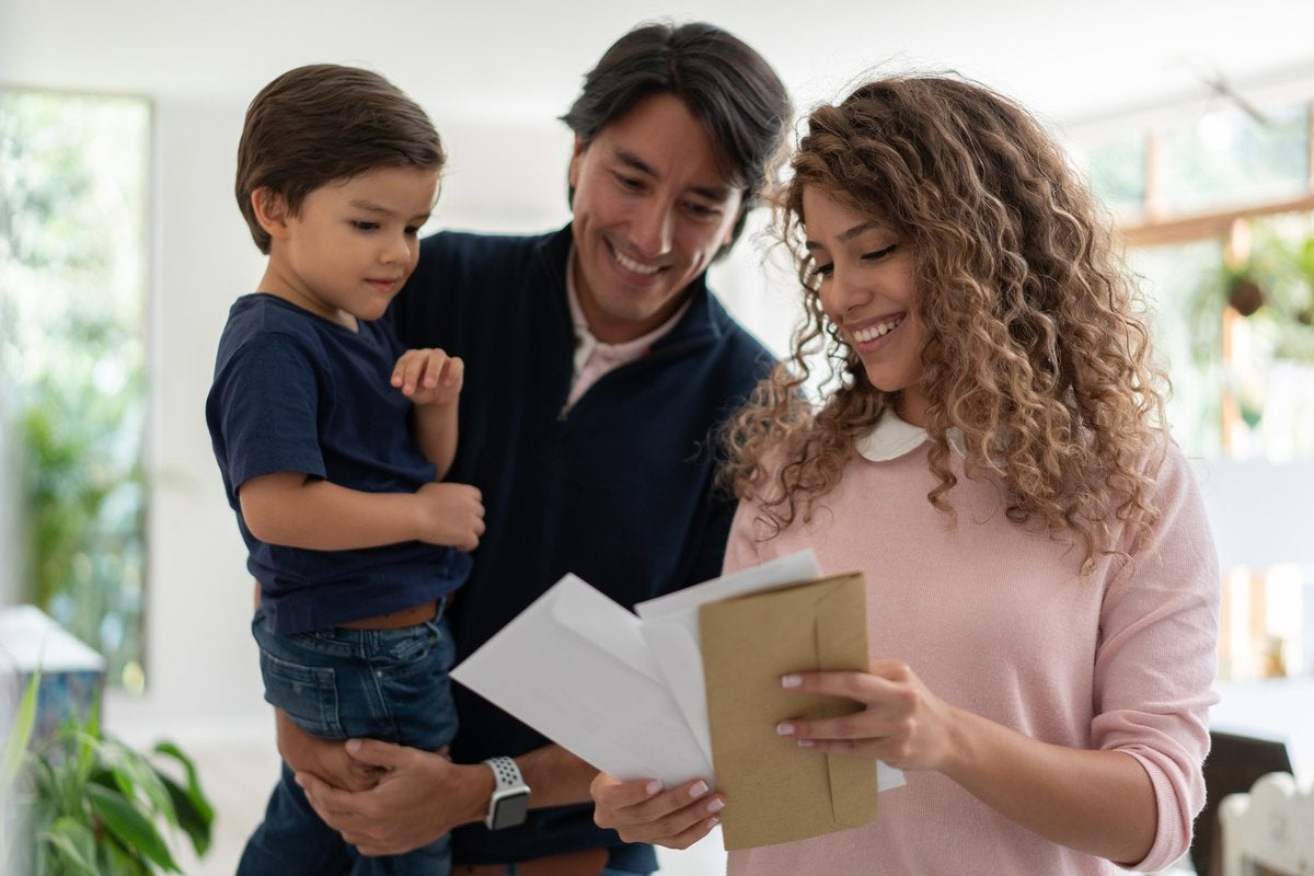 Young family smiles while looking through mail.
