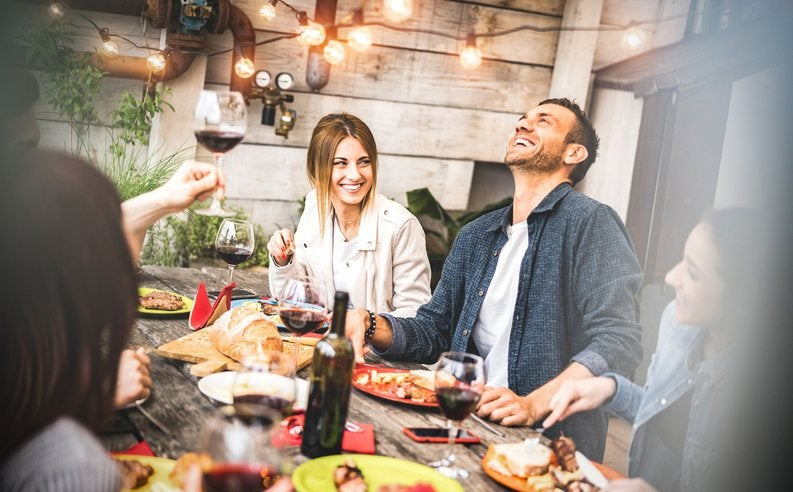A group of smiling people having wine and food at a patio table.