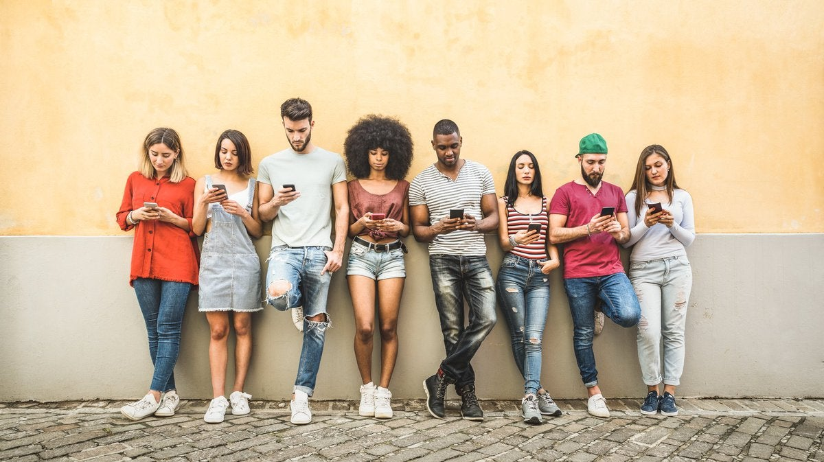 A group of young people leaning against a wall and all looking at their phones.