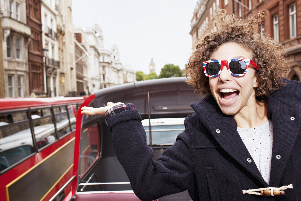 Young male traveler on a trolley in London wearing sunglasses with British flag design on them.