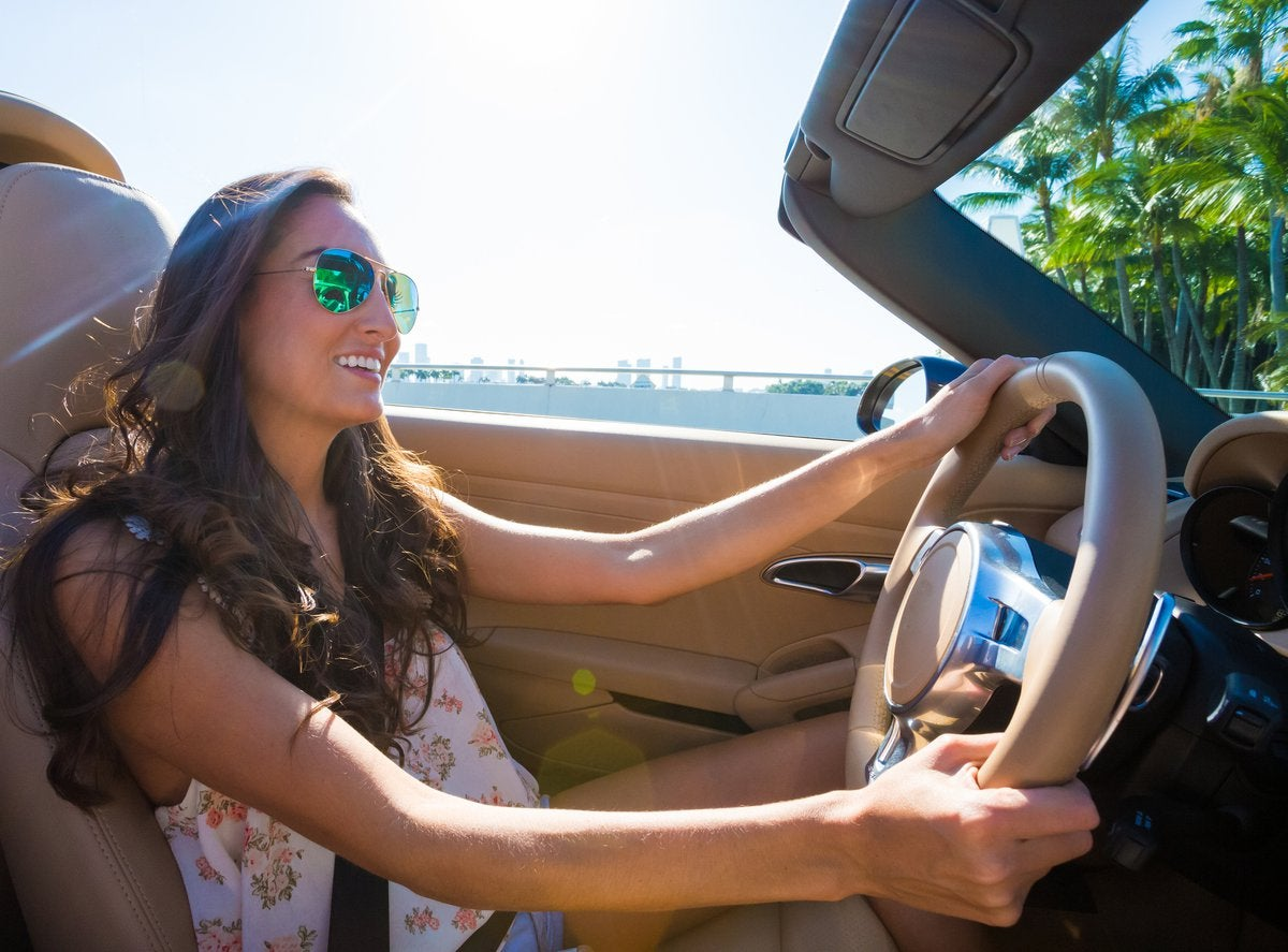Young woman driving convertible near the coast.