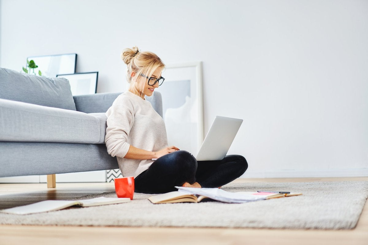 A young woman sitting on the floor working on her laptop.