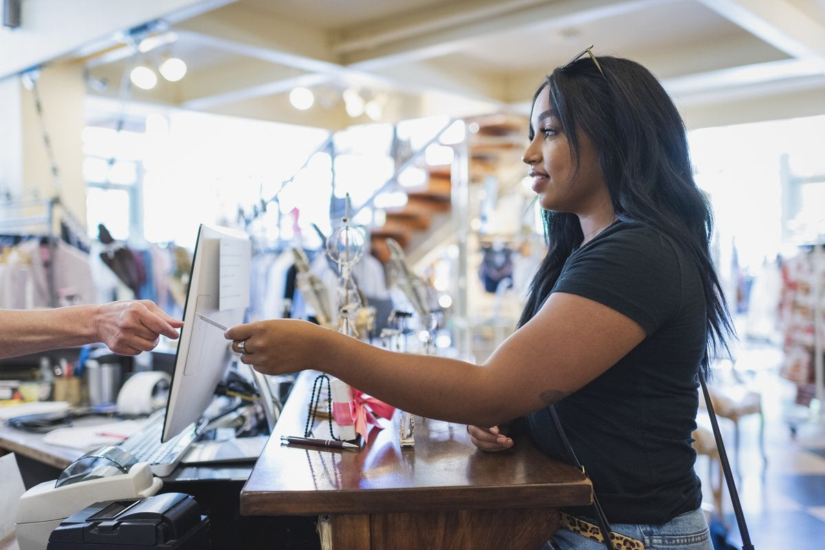 Young woman paying cashier with credit card in a clothing store