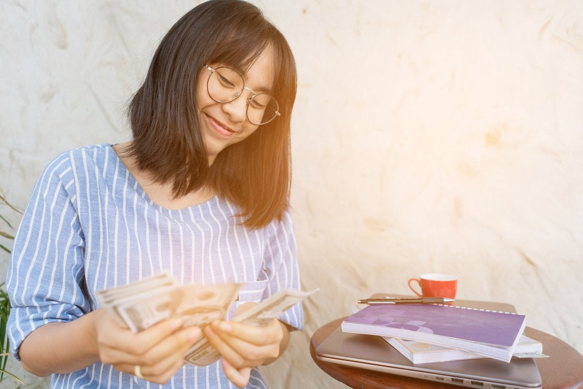 Young woman smiling as she counts cash in her hands.