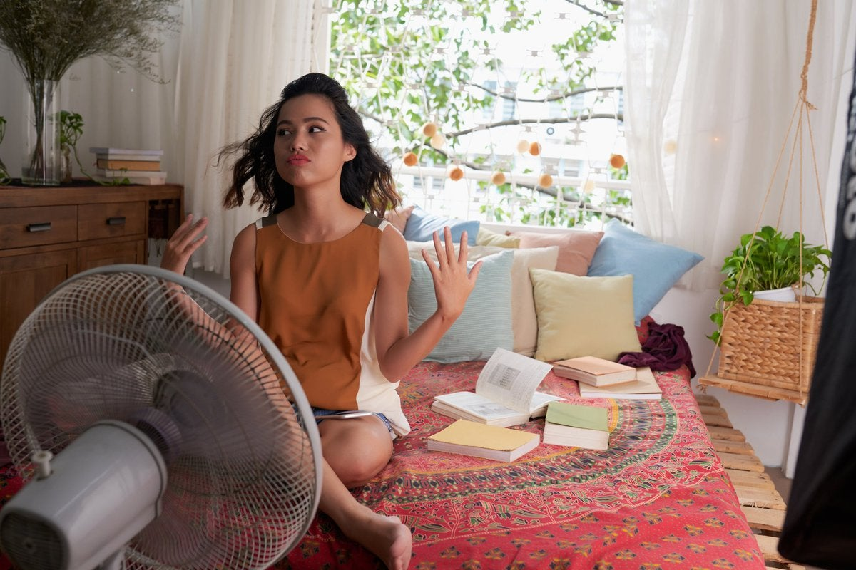 A young woman tries to stay cool while sitting on her bed in front of a fan.
