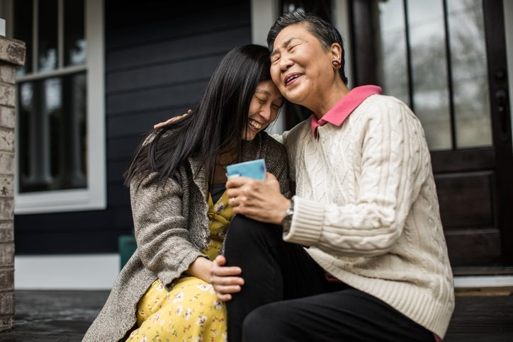 An adult woman and her senior mom sitting on their front porch steps while smiling and hugging.