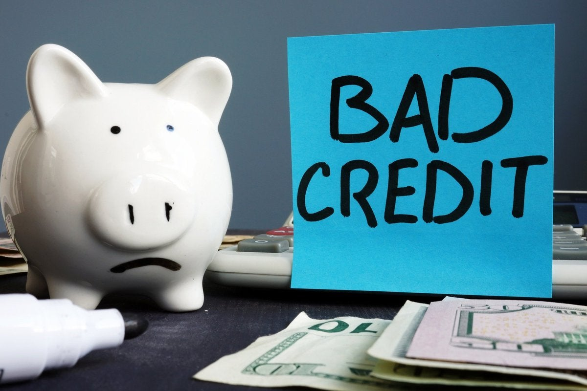"""Piggy bank next to a sign that says """"bad credit"""""""
