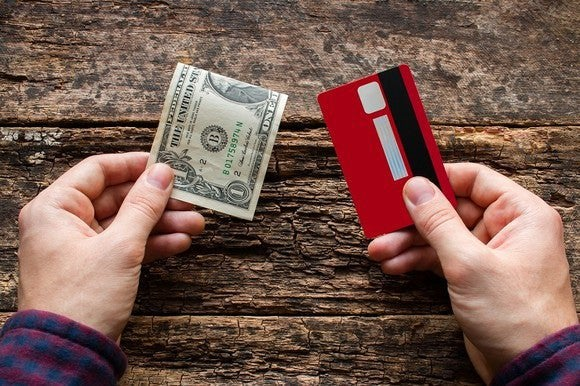 Hand holding a $1 bill and hand holding a credit card with wooden background