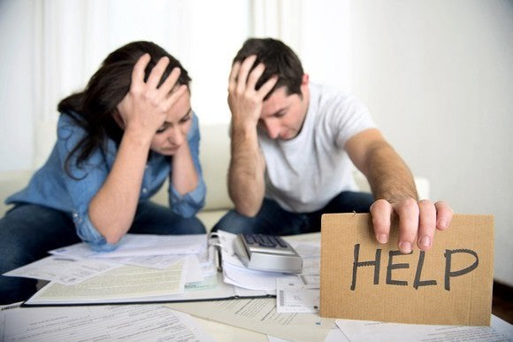 """Distraught couple looking at bills holding a sign that says """"help"""""""
