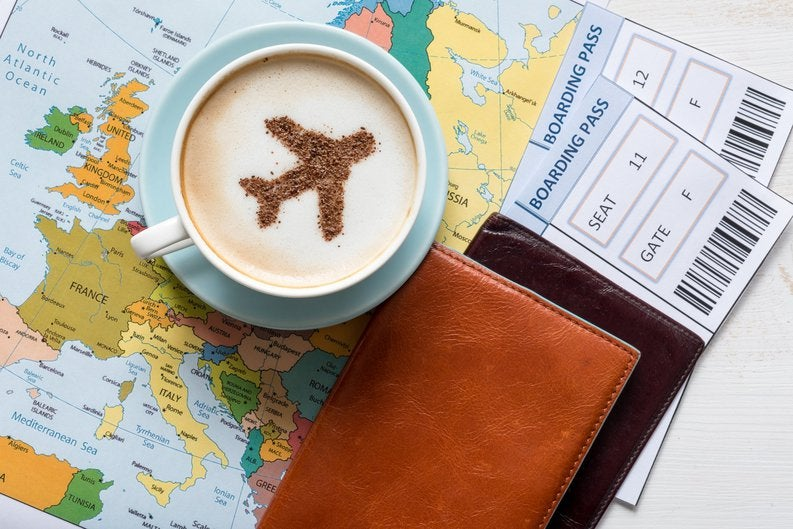 boarding passes and a latte with an airplane drawn on the foam